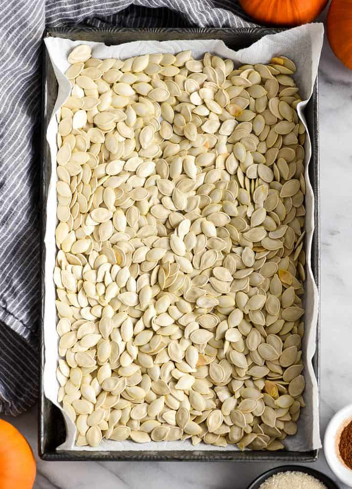 overhead view of pumpkin seeds drying in a baking pan on a paper towel