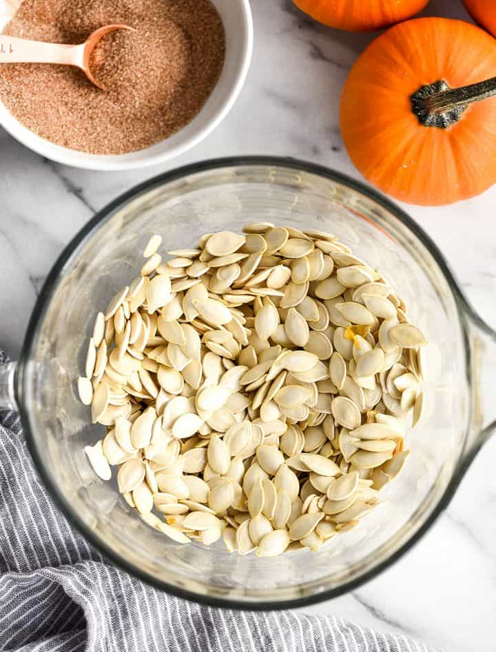 overhead view of dried pumpkin seeds in a bowl coated with butter before adding cinnamon sugar