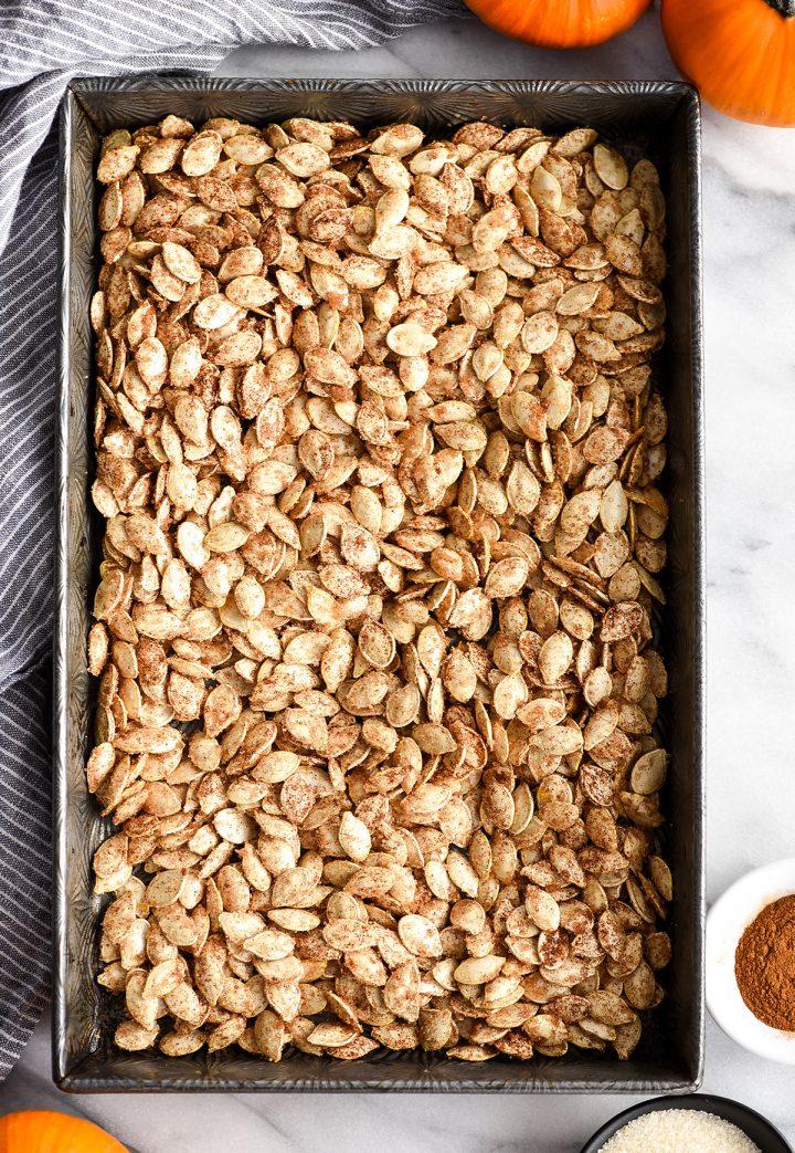 overhead view of cinnamon sugar pumpkin seeds in a baking pan before being roasted