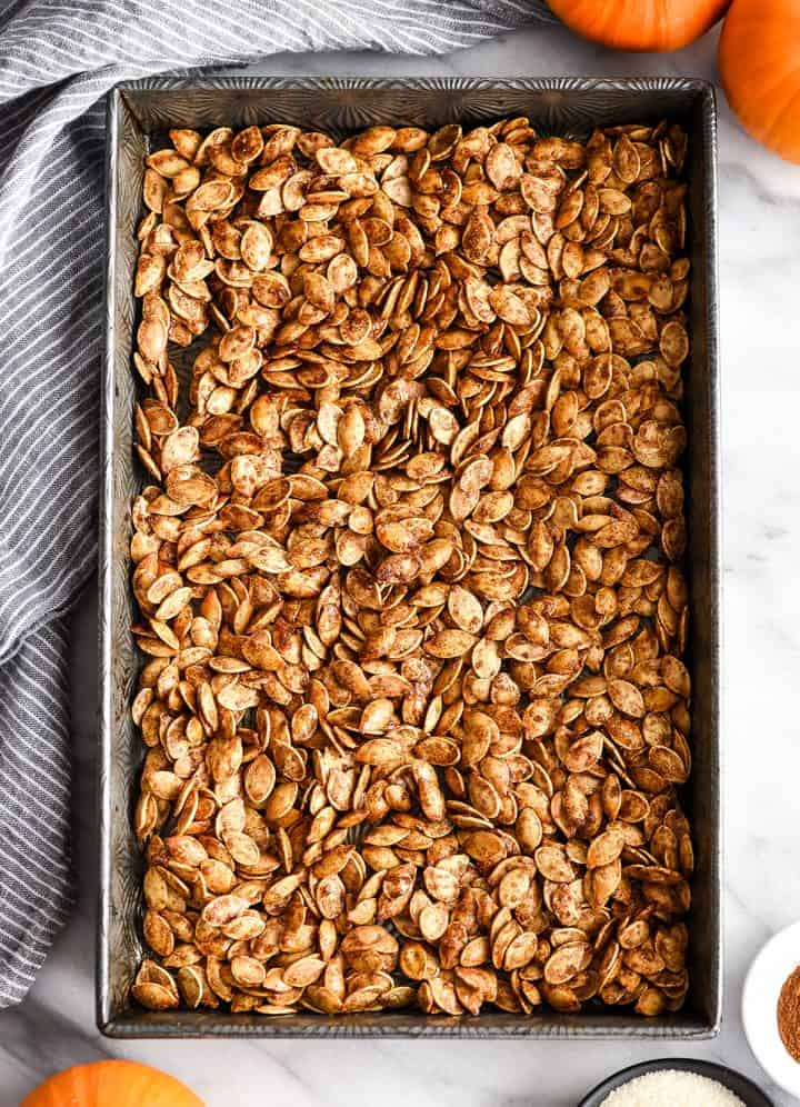 overhead view of cinnamon sugar pumpkin seeds in a baking pan after being roasted