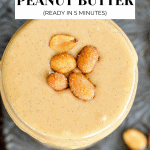 Peanut butter in mason jar with peanuts on top.
