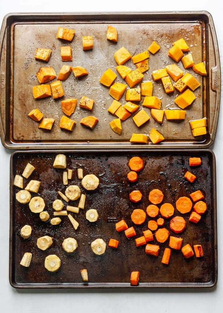 vegetables roasting on two baking sheets to make Roasted Vegetable Soup