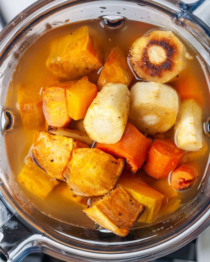roasted vegetables and broth in the contianer of a vitamix to make Roasted Vegetable Soup