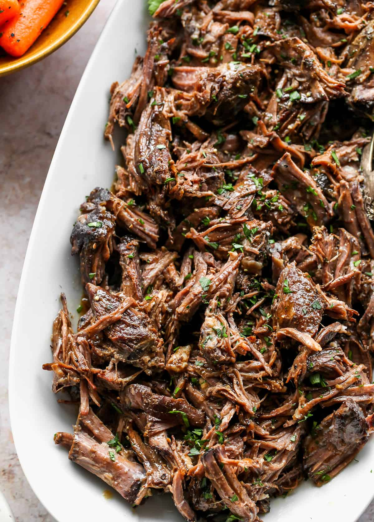 up close overhead view of a plate of shredded Balsamic Slow Cooker Pot Roast