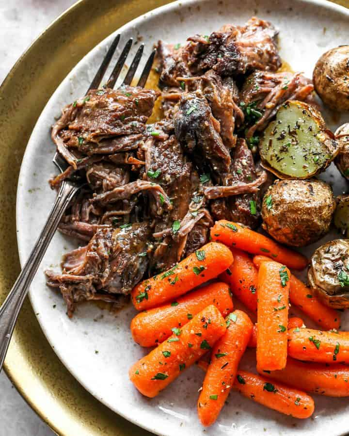 Slow Cooker Pot Roast on a plate with carrots and potaotes
