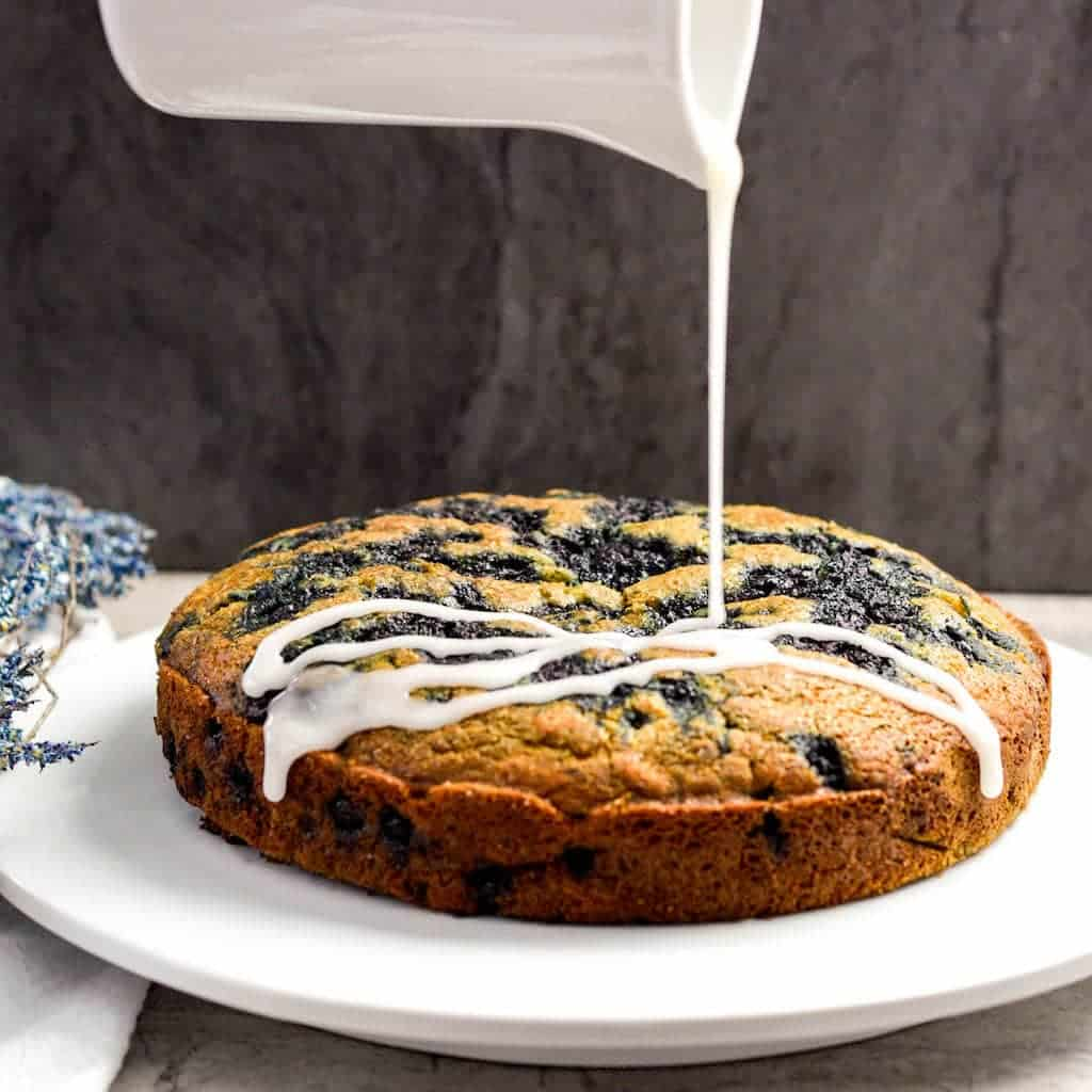 Front view of glaze being drizzled onto dairy-free Blueberry Coffee Cake