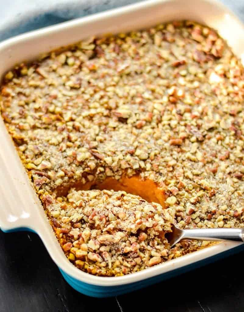 Side view of healthy sweet potato casserole with a spoon dipping into the square baking dish about to take a scoop