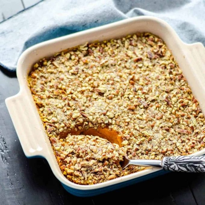 Overhead view of healthy sweet potato casserole in a square baking dish with a spoon dipping in to take a scoop
