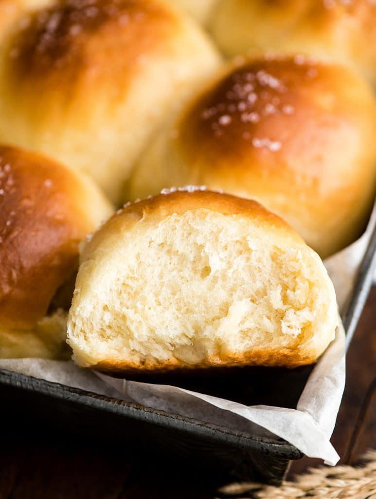up close overhead view of a Best Homemade Dinner Roll in the pan with other rolls surrounding it after baking