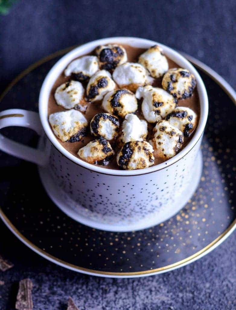 Up close side view of dairy-free hot chocolate in a mug with toasted marshmallows