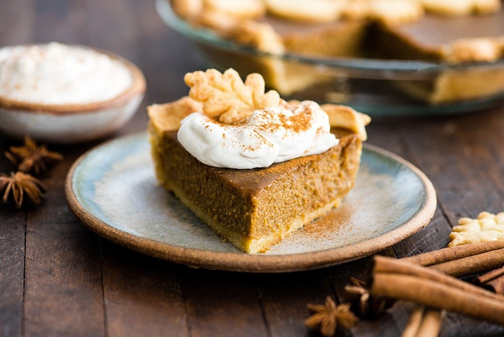 front view of a slice of dairy-free pumpkin pie on a plate with a dollop of whipped cream and a pie crust leaf on top