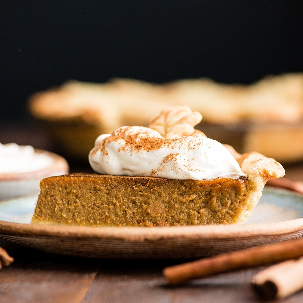 side view of a piece of dairy-free pumpkin pie on a plate with a dollop of whipped cream