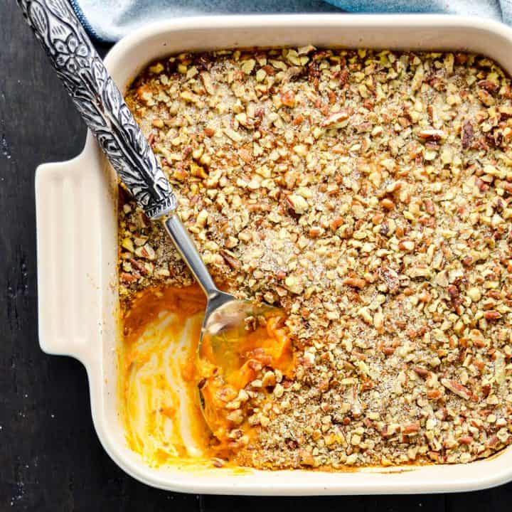 Overhead view of a healthy sweet potato casserole in a square baking dish with some missing and a spoon scooping more out of it