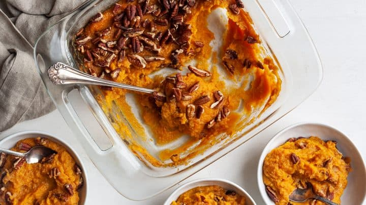 overhead view of a baking dish of healthy sweet potato casserole with some scooped out into bowls