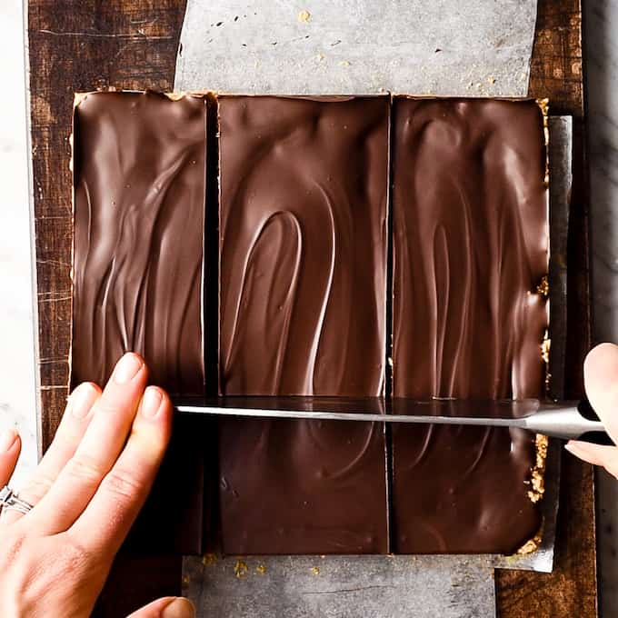 Overhead view of No-Bake Chocolate Peanut Butter Bars on a cutting board being cut into squares