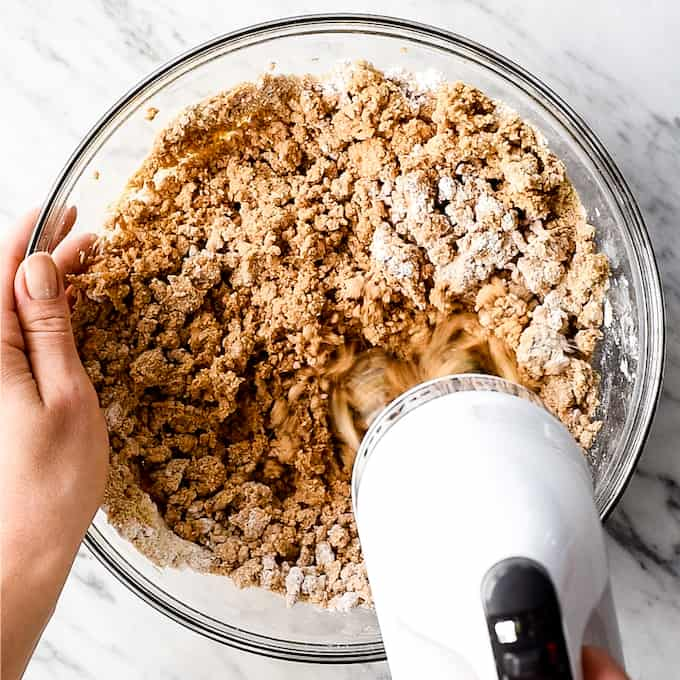 overhead view of a hand mixer mixing the ingredients to the peanut butter base layer making No-Bake Chocolate Peanut Butter Bars