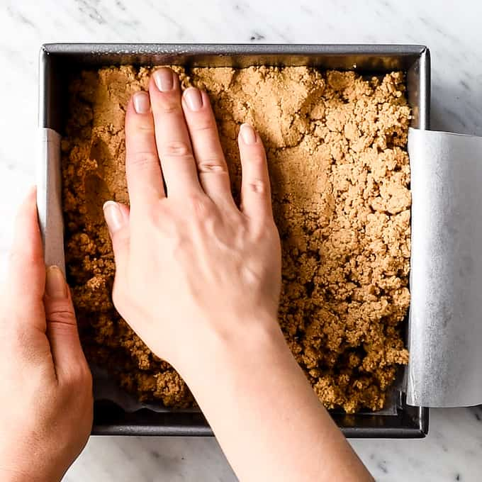 Overhead view of hands pressing down the peanut butter layer into the pan of these No-Bake Chocolate Peanut Butter Bars