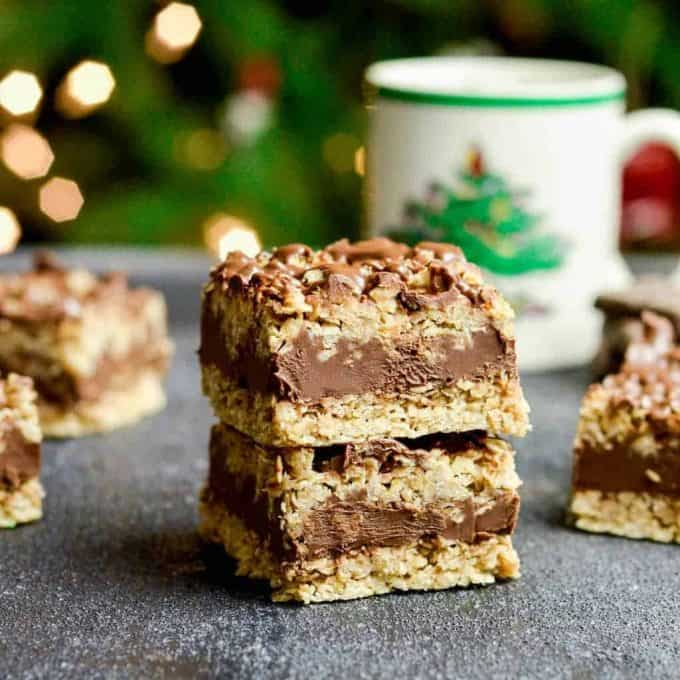 Front view of two No-Bake Chocolate Peanut Butter Oatmeal Bars stacked on each other with a Christmas tree in the background