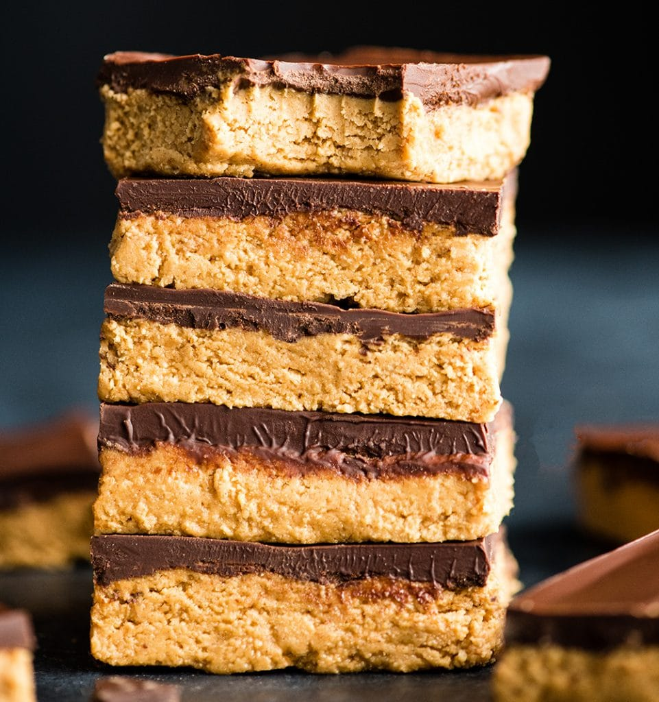 front view of a stack of five No-Bake Chocolate Peanut Butter Bars, the top one has a bite taken out of it