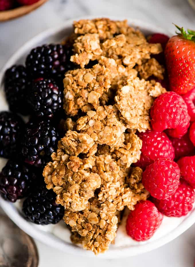 Up close overhead view of peanut butter granola in a bowl of yogurt and berries