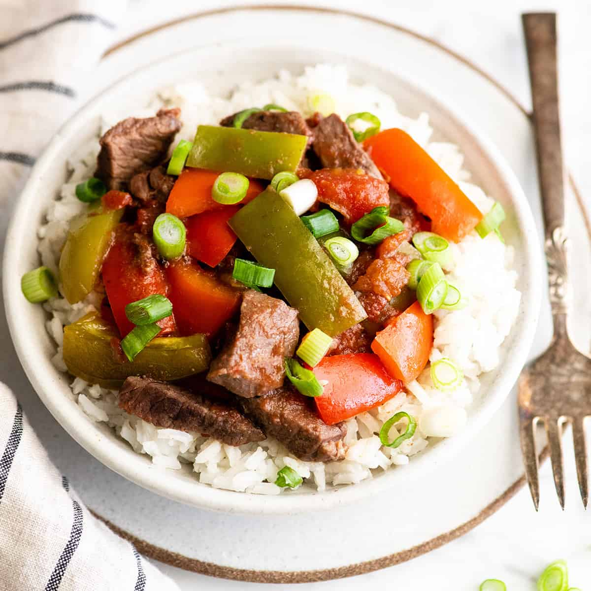 overhead view of slow cooker pepper steak in a bowl over rice