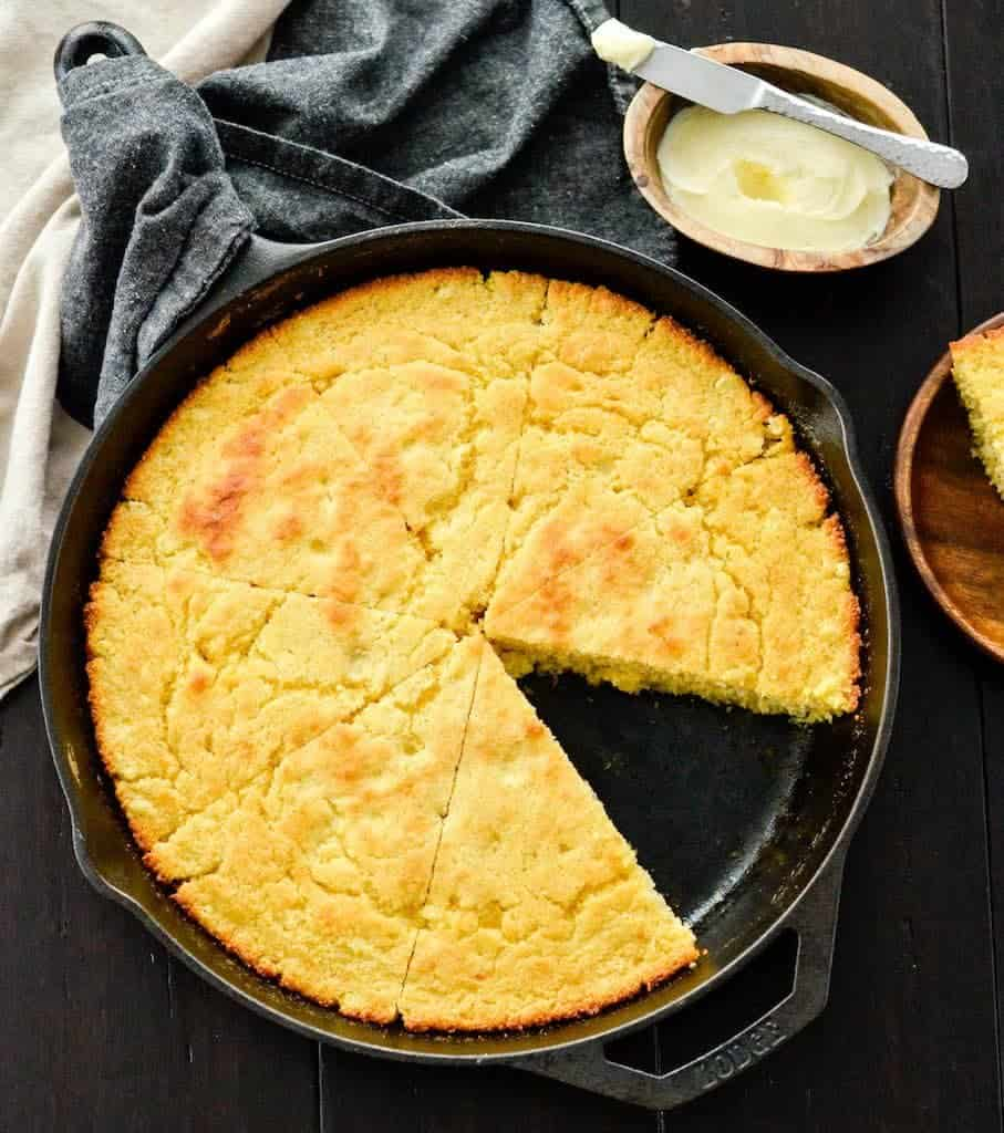 Overhead view of Healthy Skillet Cornbread cut into 8 pieces in a cast iron skillet with one piece removed