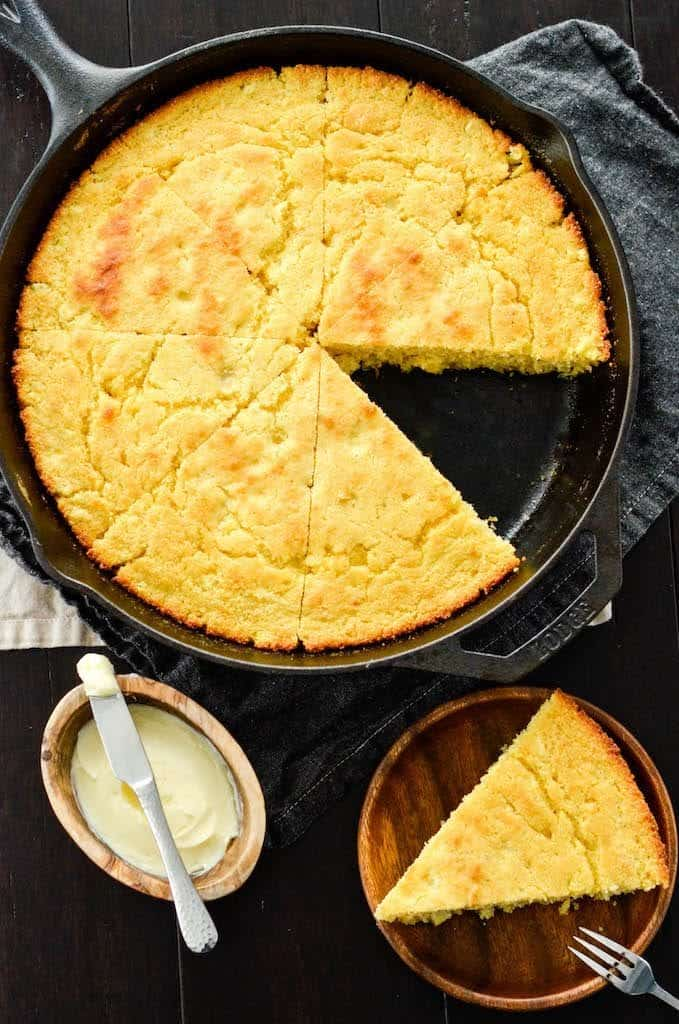 Overhead view of healthy skillet cornbread recipe in a cast iron skillet cut into 8 pieces with one removed on a plate next to the skillet