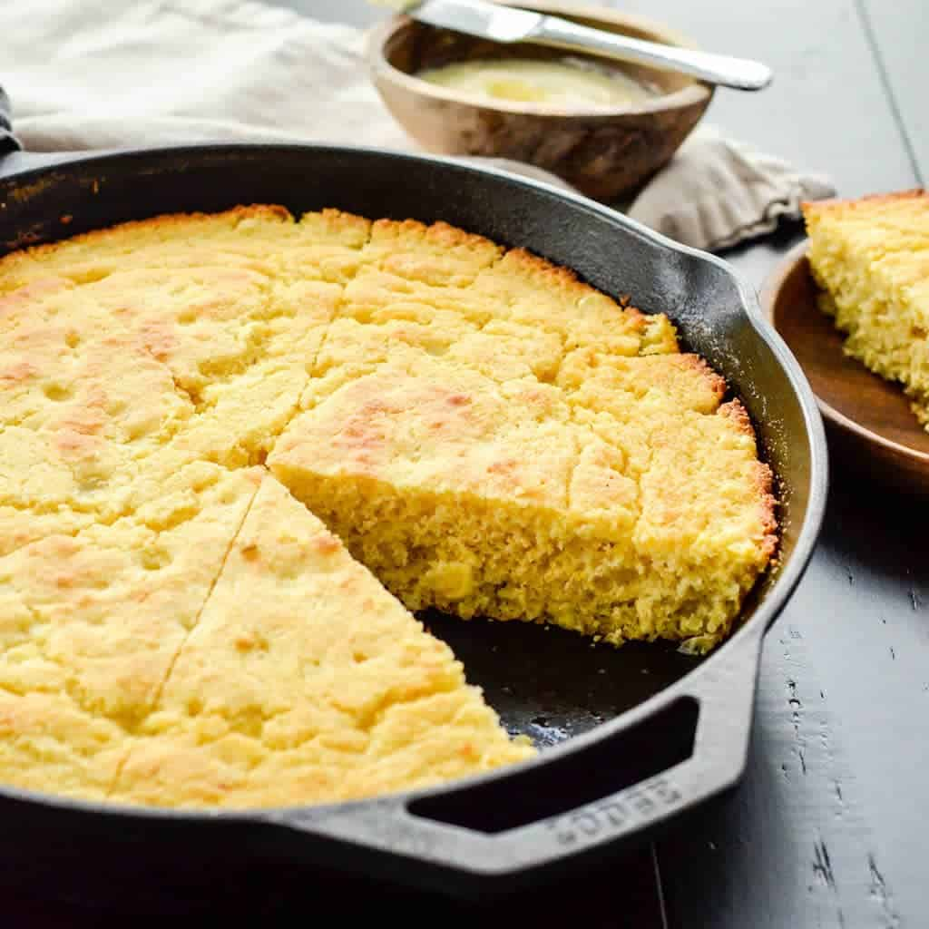 Side view Healthy Skillet Cornbread recipe in a cast iron skillet cut into pieces with one removed