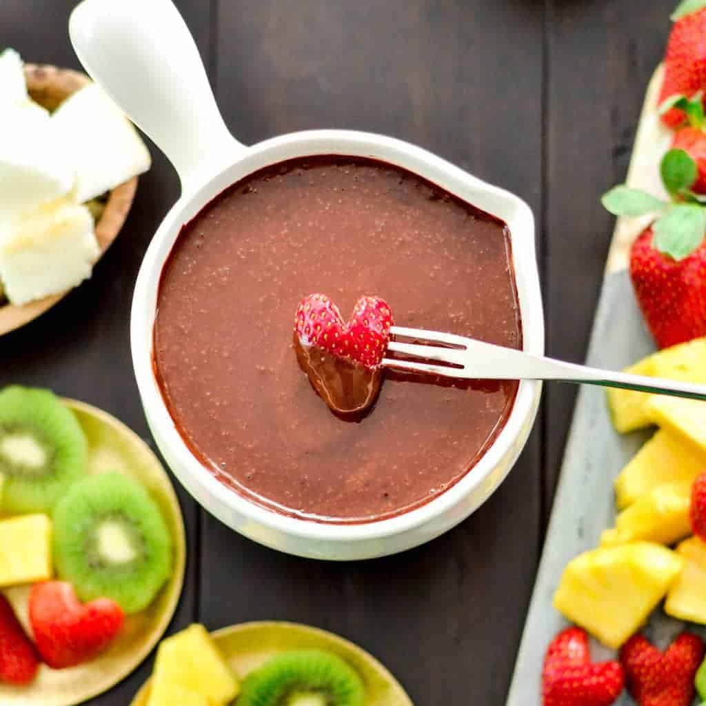 Overhead view of a heart-shaped strawberry being dipped into a bowl of Vegan Chocolate Fondue