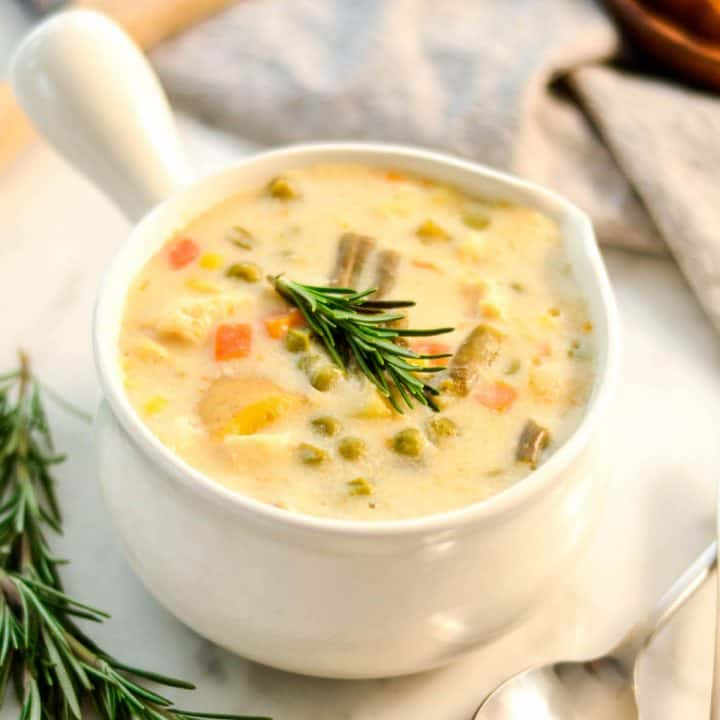 overhead view of Slow Cooker Chicken Pot Pie Soup in a white soup bowl with a handle