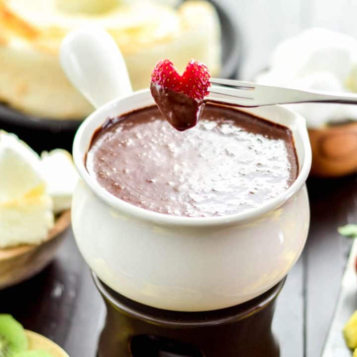 Front view of a heart-shaped strawberry that has been dipped into Vegan Chocolate Fondue