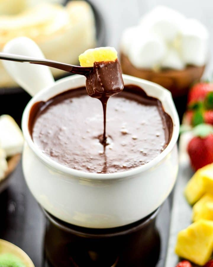 Front view of a piece of pineapple being dipped into a bowl of Vegan Chocolate Fondue