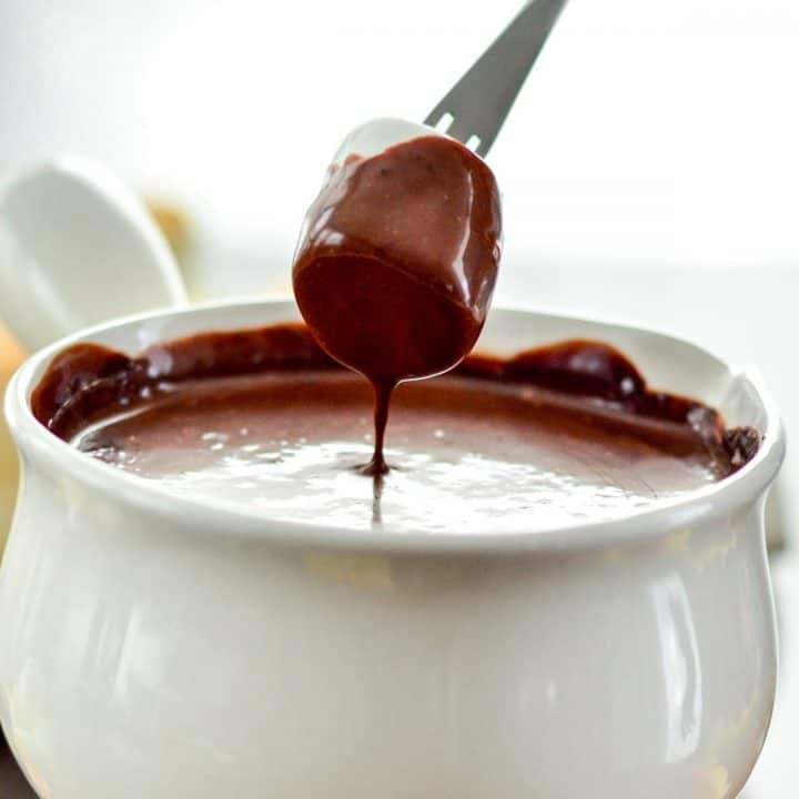 Front view of a marshmallow being dipped into Vegan Chocolate Fondue