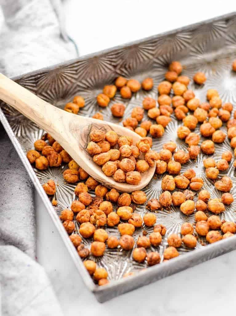 Overhead view of a pan of crunchy roasted chickpeas with a spoon in it scooping some out