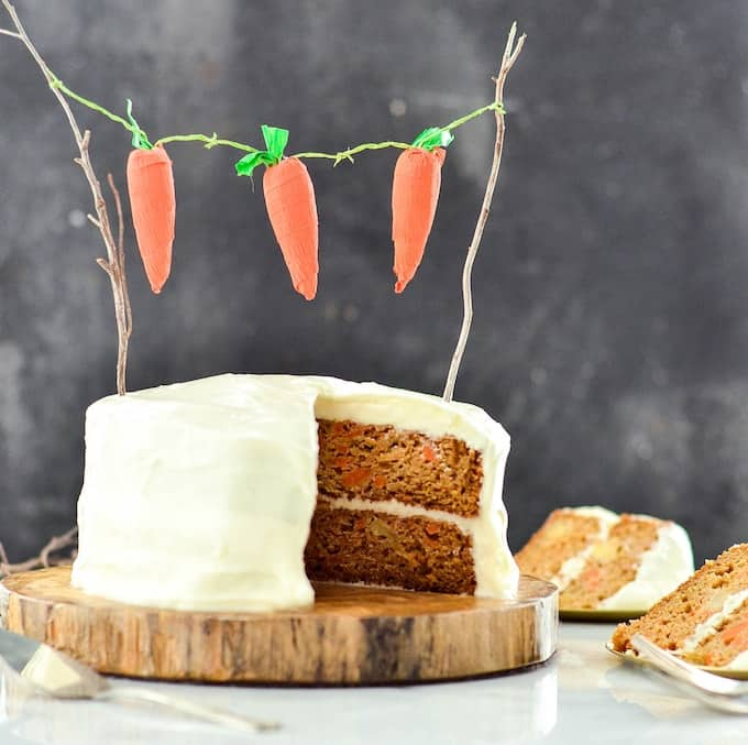 Front view of a healthy carrot pineapple cake with two slices cut out of it sitting on plates next to the cake