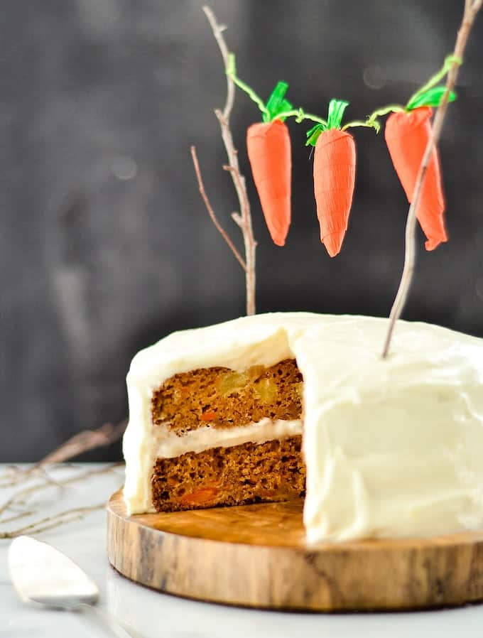 Side view of a healthy pineapple carrot cake on a log cake stand