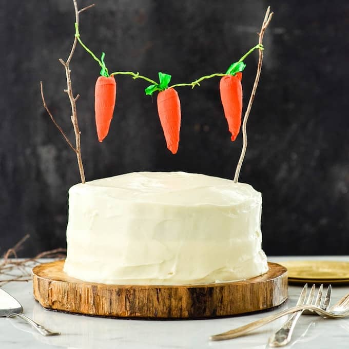 front view of a healthy carrot pineapple cake with carrot bunting connected with twigs on a log cake stand