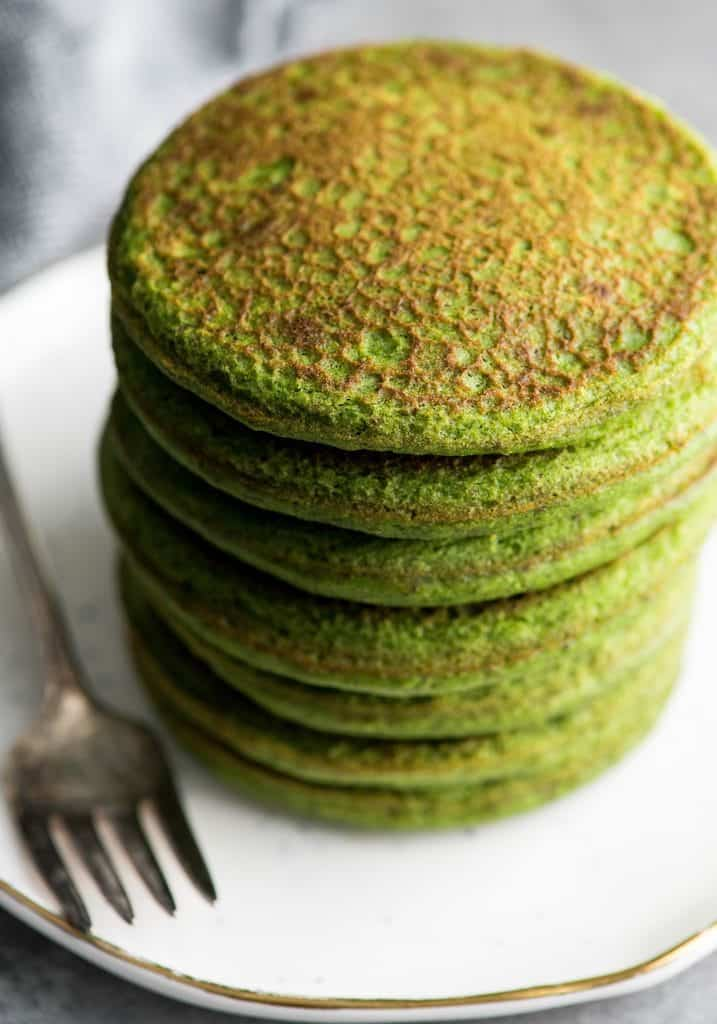Side/overhead shot of a stack fo 7 gluten-free spinach oatmeal pancakes right after they are cooked before adding any toppings