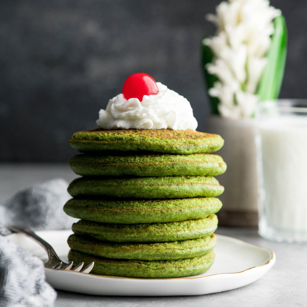 Side view of a stack of 7 gluten-free spinach oatmeal pancakes on a plate topped with whipped cream and a cherry before adding syrup