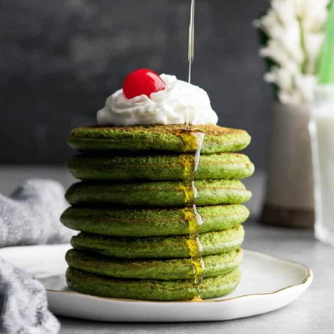 front view of maple syrup being poured onto a stack of 7 gluten-free spinach oatmeal pancakes on a plate topped with whipped cream and a cherry