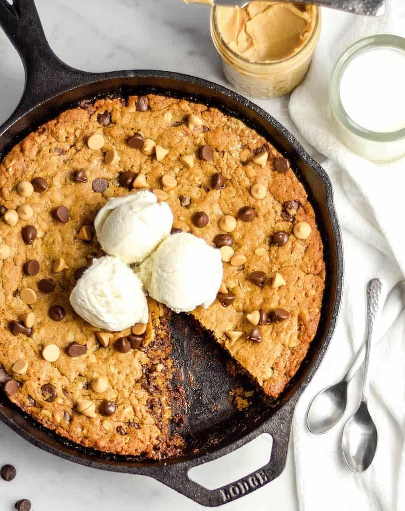 Overhead view of Healthy Skillet Peanut Butter Cookie with ice cream on top and one triangular piece cut out