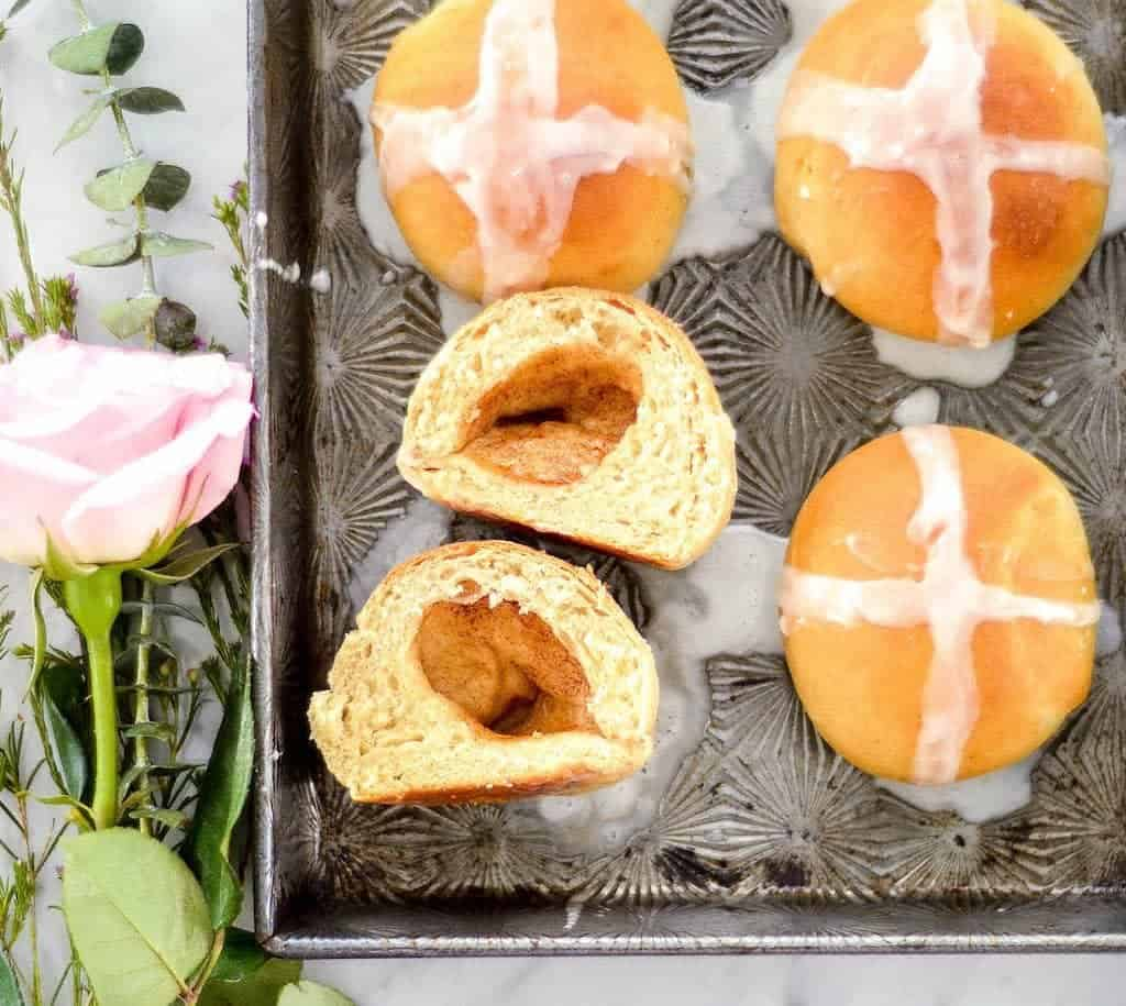 Overhead view of homemade resurrection rolls on a baking pan with one cut in half and open showing the