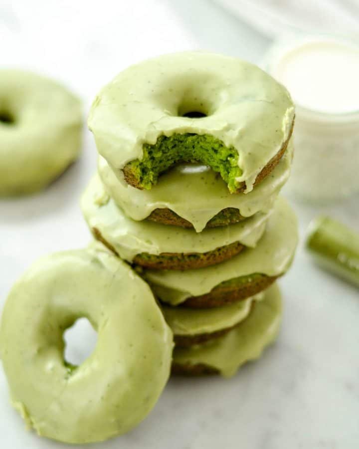 front view of a stack of 6 Paleo Spinach Donuts the top one has a bite taken out of it