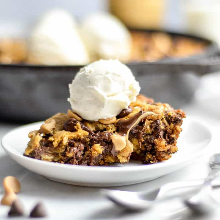 Front view of a piece of Healthy Skillet Peanut Butter Cookie on a plate with a scoop of ice cream on top