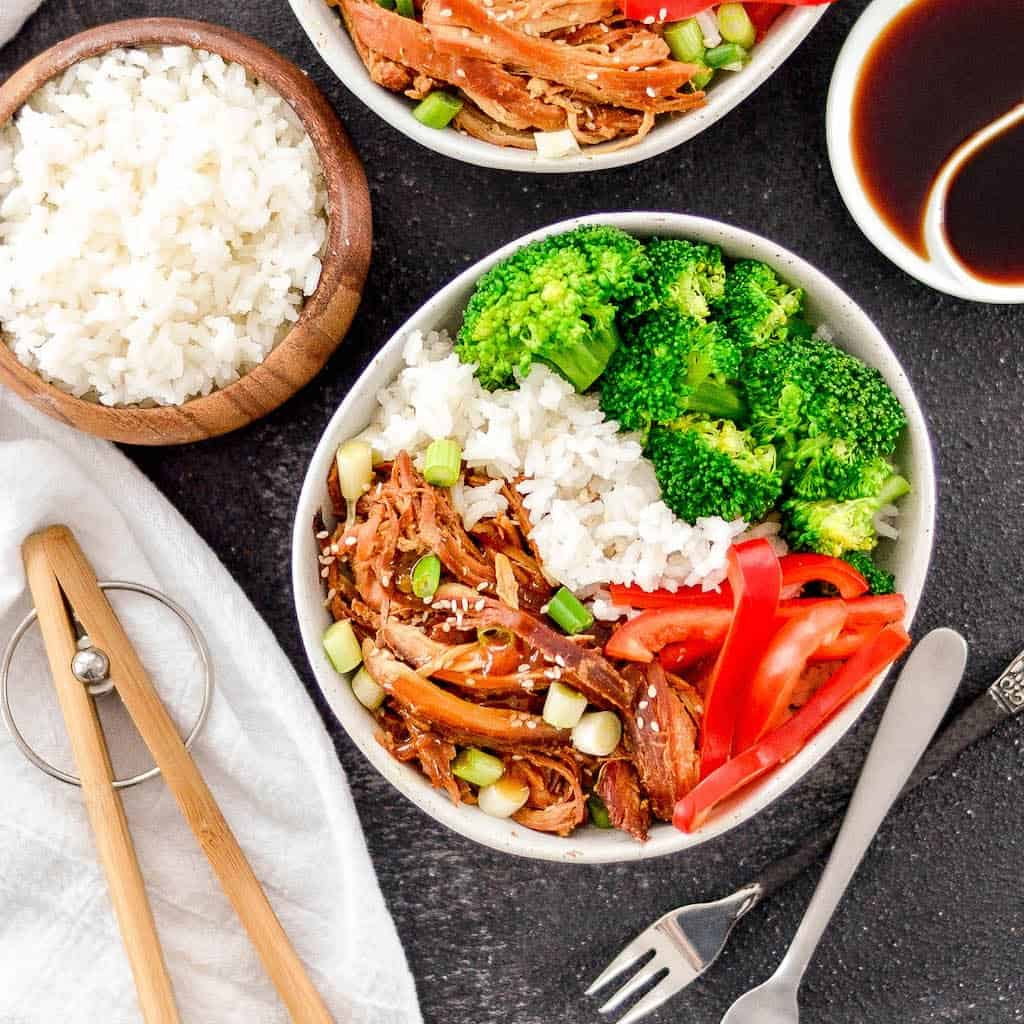 Overhead view of two bowls of Slow Cooker Teriyaki Chicken with rice and vegetables