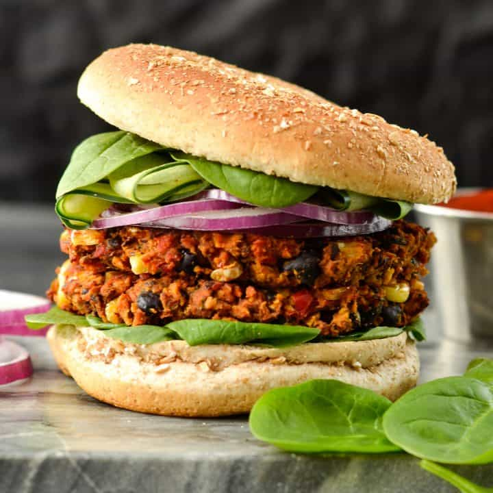 Front view of a Baked Black Bean Sweet Potato Burger with two patties on a bun with lettuce and red onion