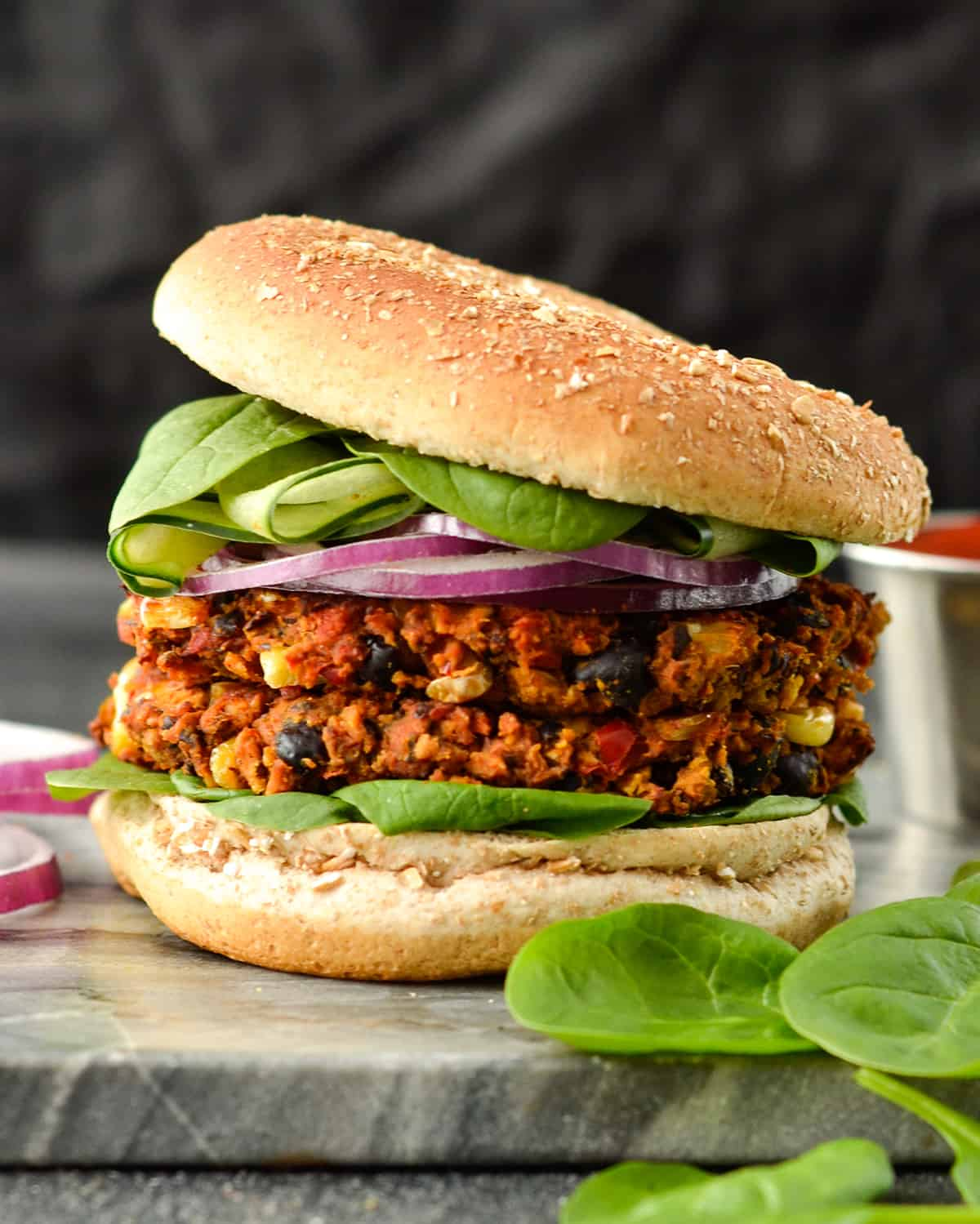 Front view of a Baked Black Bean & Sweet Potato Veggie Burgers with two patties on a bun with lettuce and red onion