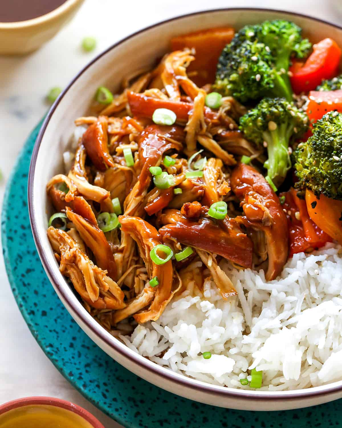 up close front view of a bowl of crockpot teriyaki chicken with veggies and rice