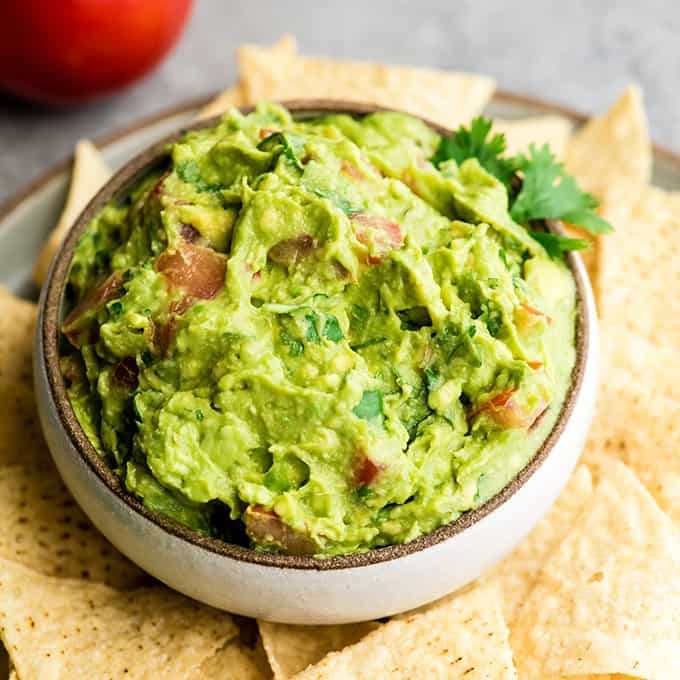 overhead view of a bowl of homemade guacamole recipe with chips around it