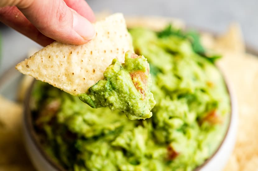 up close front view of a hand holding a chip with guacamole on it